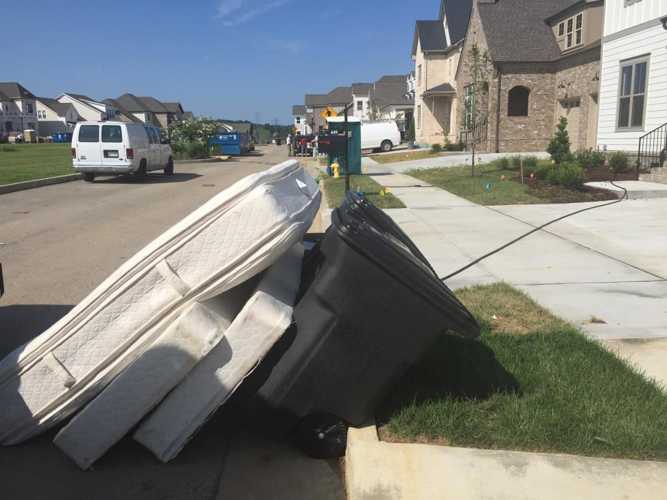 Picture of three mattresses leaning against a trash bin sitting curbside