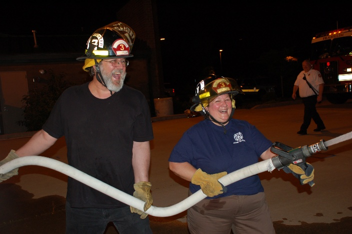 Two smiling participants in the Citizens' Fire Academy hold a fire hose