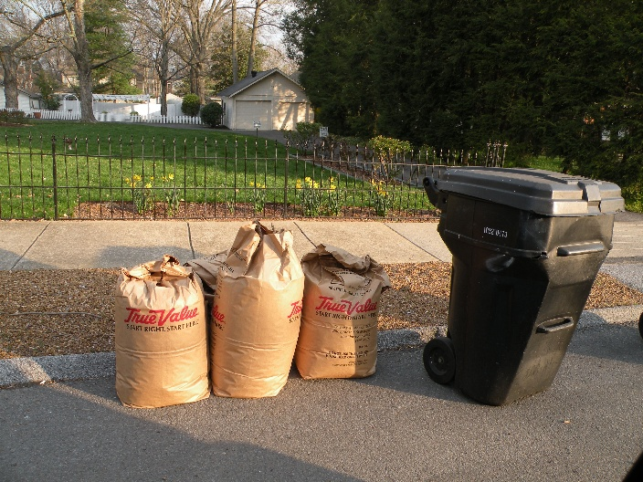 Picture of three leaf collection bags sitting next to a trash bin curbside